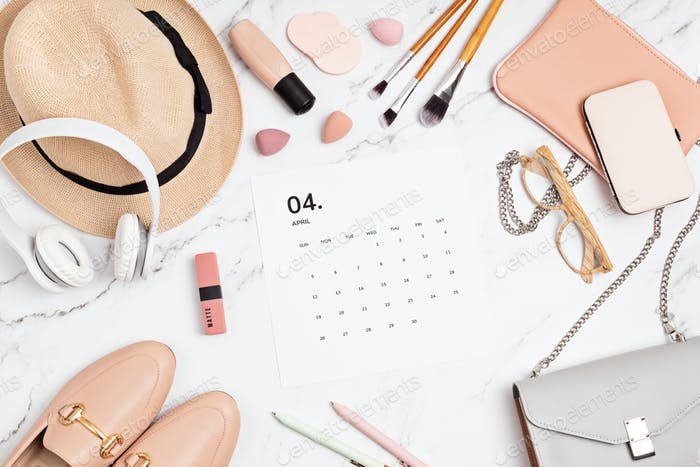 Flat lay with calendar for april with woman fashion spring accessories