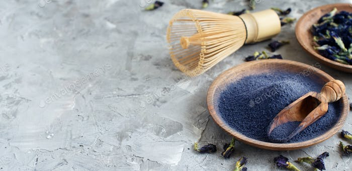 Butterfly pea blue matcha powder word with wrisk and dried flowers