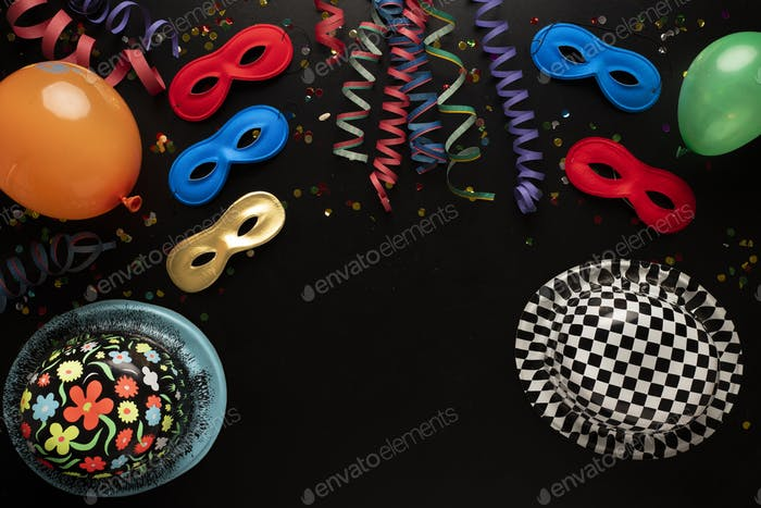 Carnival objects on a black background. Coiled streamers, masks, hats, paper skeleton, confetti