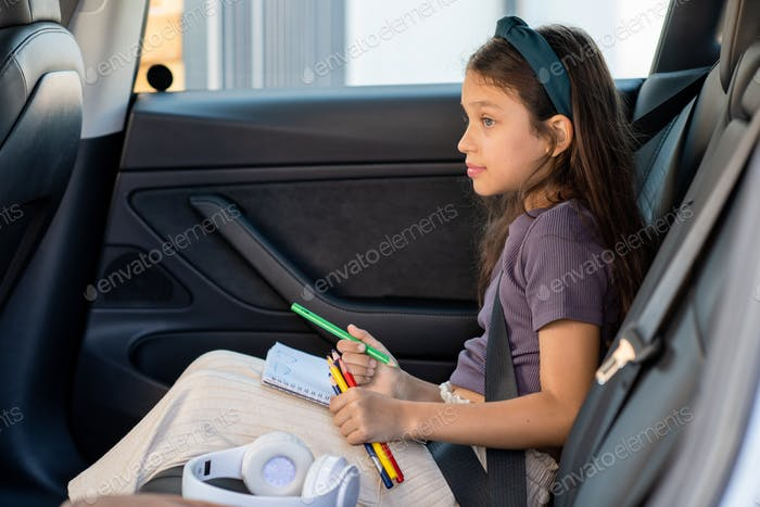 Cute little girl with crayons waiting parents in car