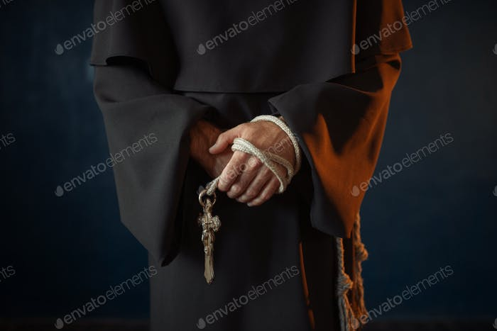 Monk holds wooden rosary and cross in hands