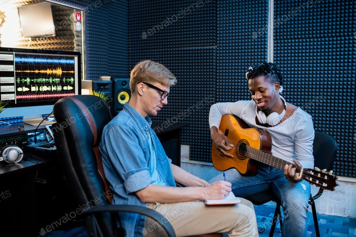 Two young multicultural men working over new song in sound recording studio