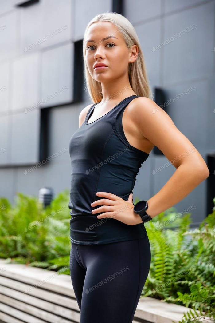 Confident Female Urban Jogger Standing With Hand On Waist