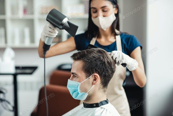 Maestro en la máscara protectora de secado del cabello del cliente en la máscara en el salón, de cerca