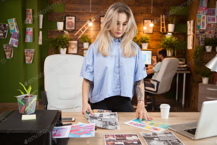 Businesswoman in creative office looking at drawings