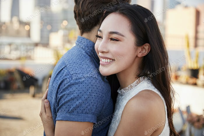 Couple Embracing On Rooftop Terrace With City Skyline In Background
