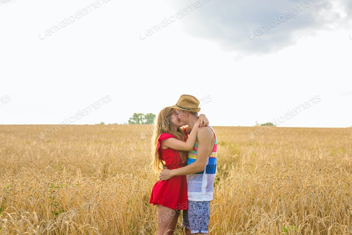 young couple kissing in a field