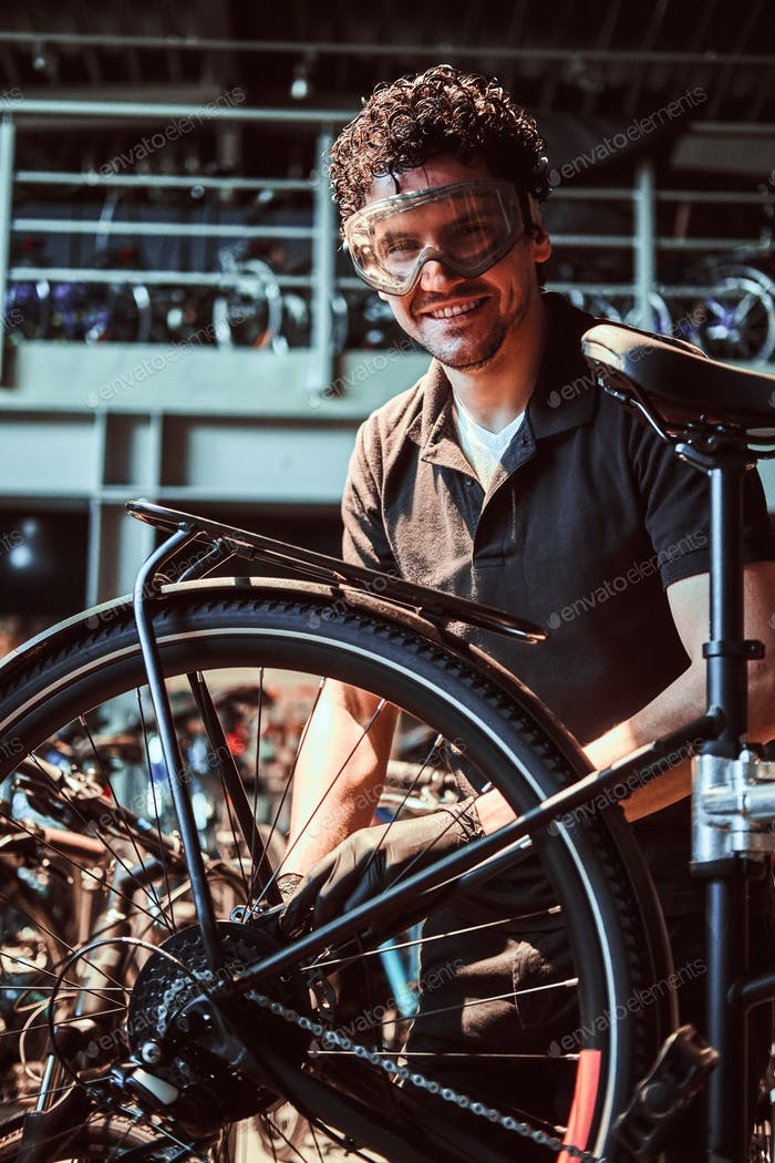 Pensive diligent master in protective glasses is fixing bicycle at workshop