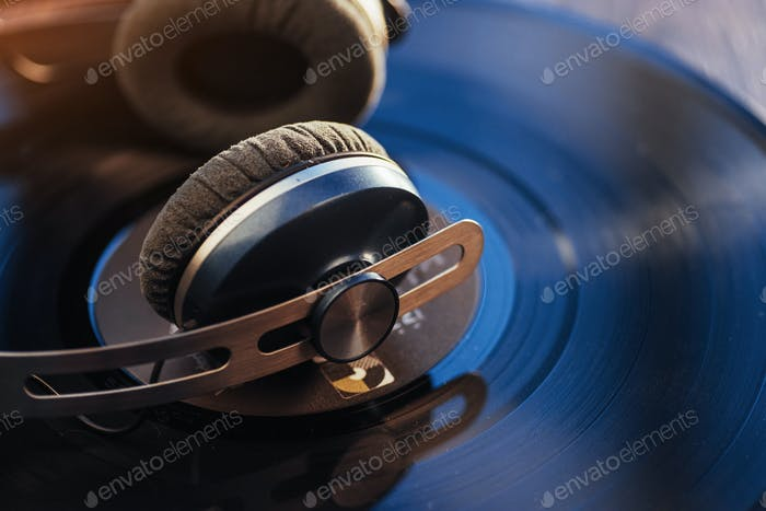 vinyl record and headphone over wooden table