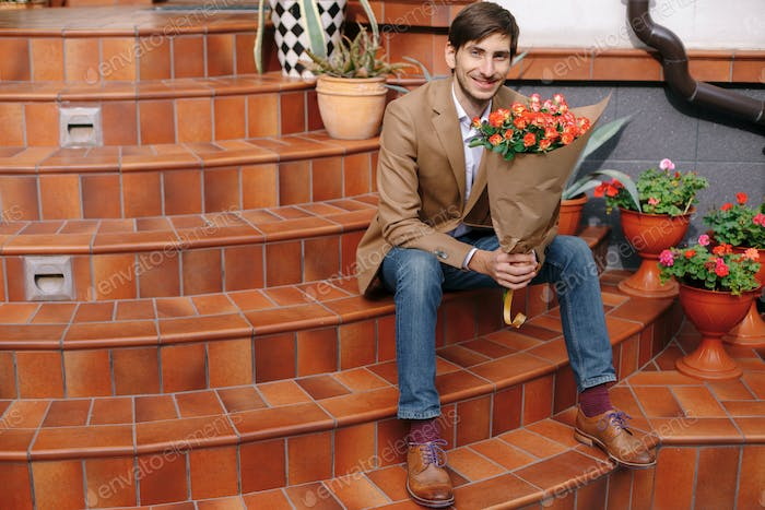 Smiling handsome man holding a bunch of roses looking to camera