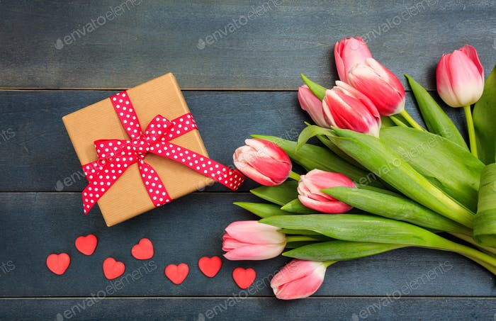 Women's day. Pink tulips and a gift on blue background, top view