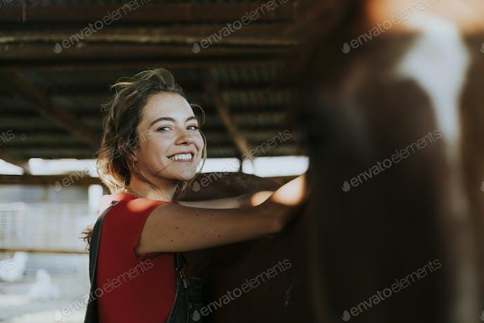 Girl grooming a chestnut horse