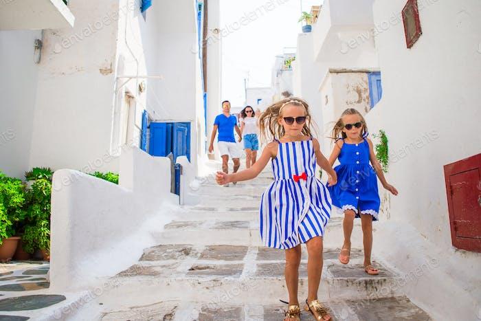 Familienurlaub in Europa. Eltern und Kinder auf der Straße des typisch griechischen traditionellen Dorfes auf
