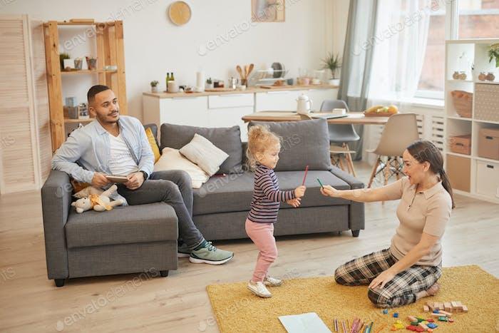 Junge Familie spielen mit Little Kid zu Hause