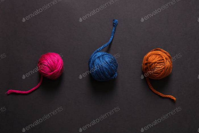 Colorful yarn clews on black background