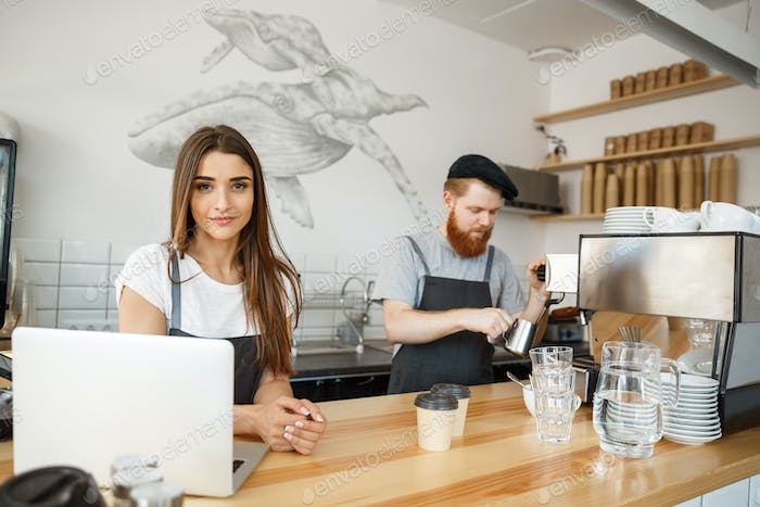 Coffee Business Concept - Positive young bearded man and beautiful attractive lady barista couple