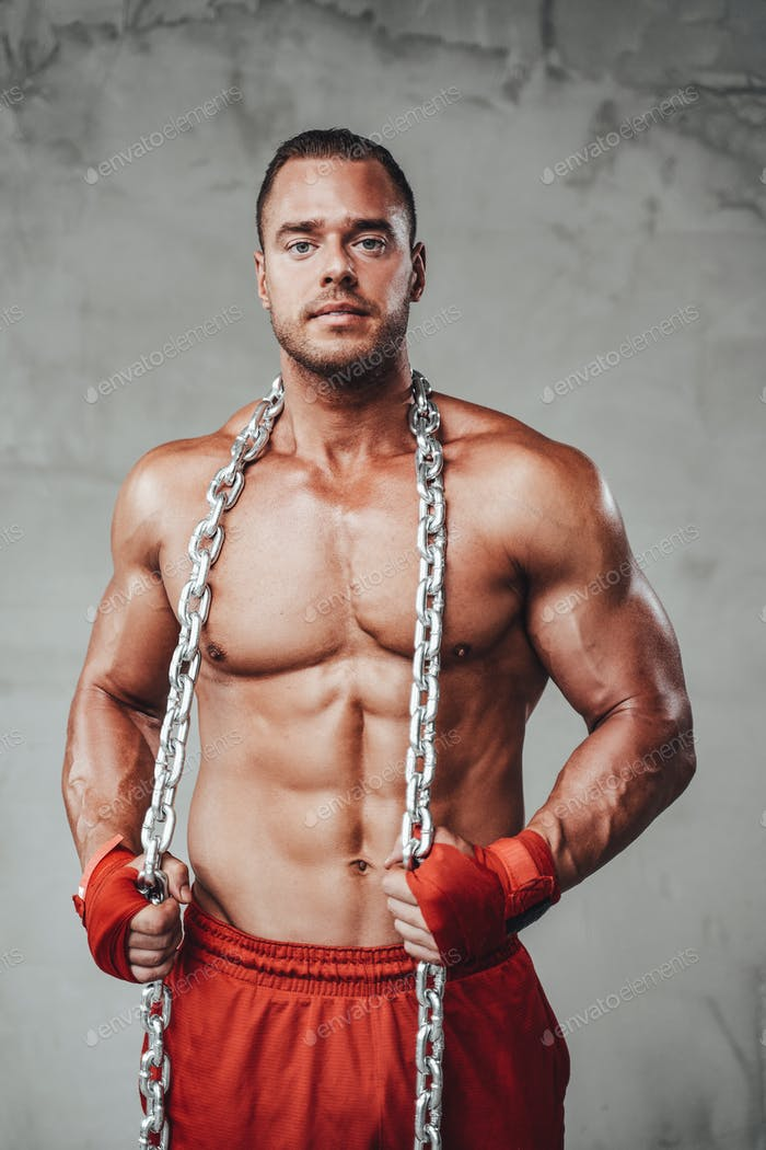 Seductive muscular guy with strong arms and metal chains