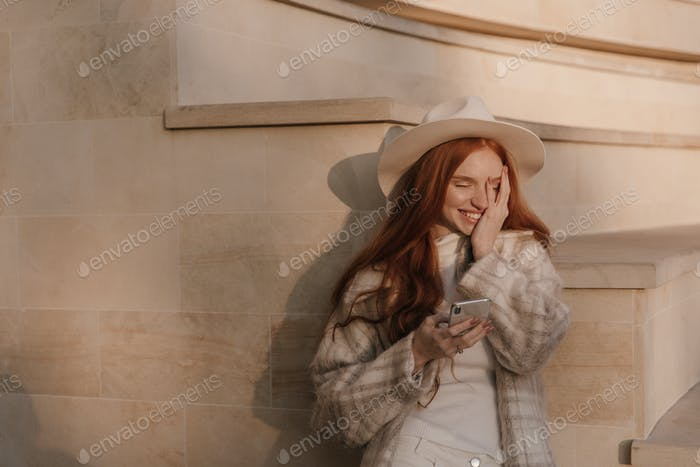 Gadgets, electronic, technology, communication concept. Attractive young red-haired lady with light