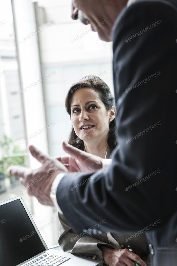 Кавказская предпринимательница, слушая разговор на деловой встрече.