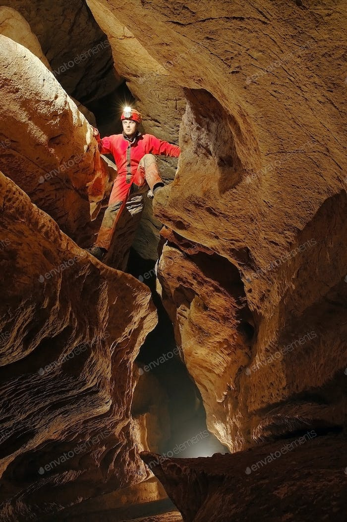 Spelunker exploring a cave passage