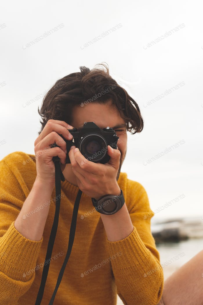 Front view of young Caucasian man using digital camera sitting on the beach