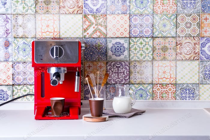 Home espresso machine on kitchen countertop with two cups, milk and sugar on sticks. Making coffee