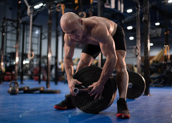 Лысый старший спортсмен готовится к тренировке по тяжелой атлетике