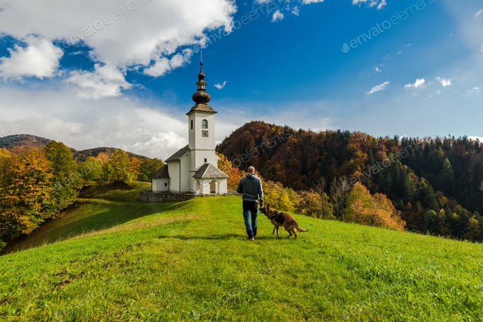 Man walking toward rural church in Slovenia