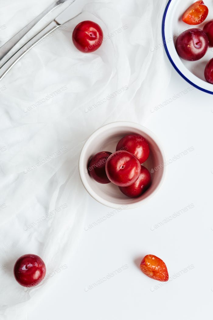 Vertical View of Fresh Plums Scattered on Table