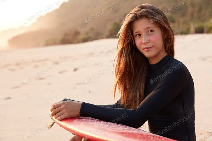 Contemplative Caucasian young woman with long hair, surf zinc on cheeks, carries surfboard, looks pe