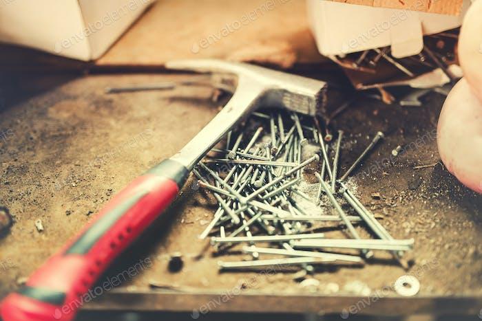Bauwerkzeuge, Zimmereihammer und Nägel in der Werkstatt. Soft-Effekt auf dem Foto