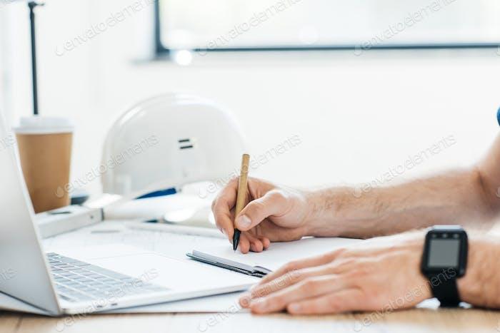 foto recortada de persona que lleva un reloj inteligente y toma notas en el lugar de trabajo
