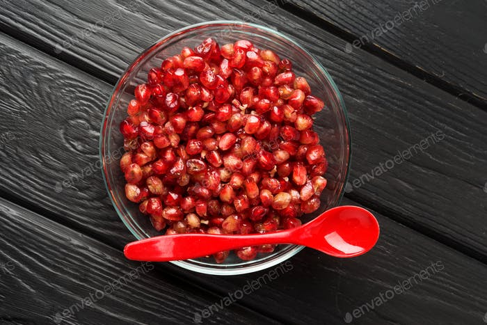 group of pomegranate grains in glass bowl on black wood