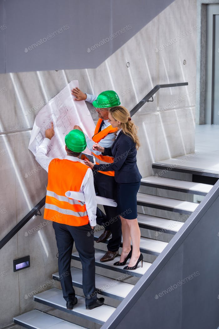 Businesswoman and architects standing on a staircase discussing with blueprint