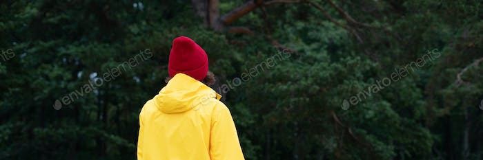 Long width banner with back view of woman in pine forest in autumn day. Local travel and adventure