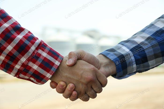 Businessmen shake hands against silos. Agriculture business