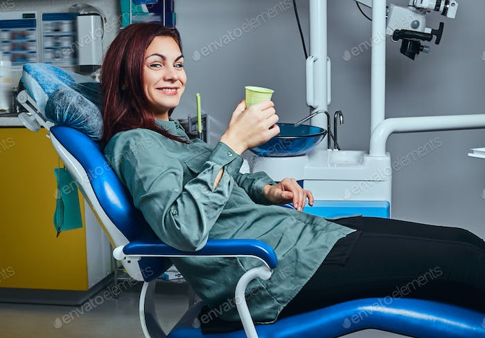 Happy woman sitting in a dentist chair holding a cup with mouthwash in a clinic.
