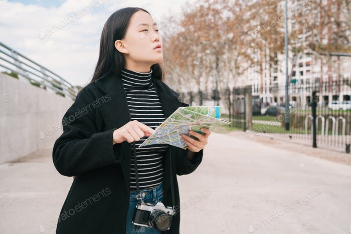Young asian woman with a map.