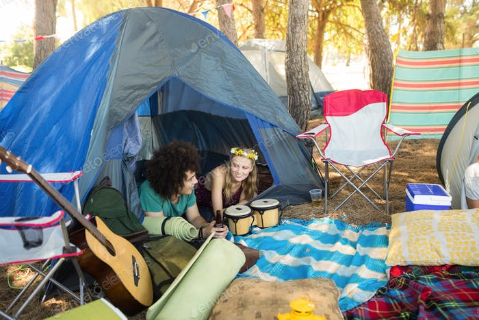 Couple talking while relaxing in tent