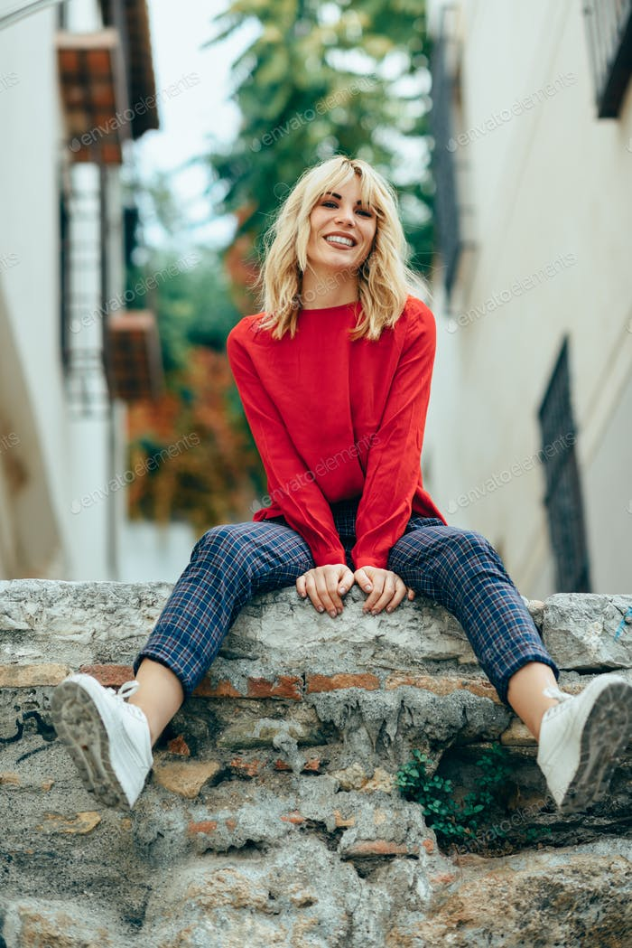 Smiling blonde girl with red shirt enjoying life outdoors.