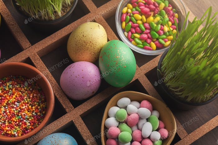 Colored easter eggs, grass and small candies in frame