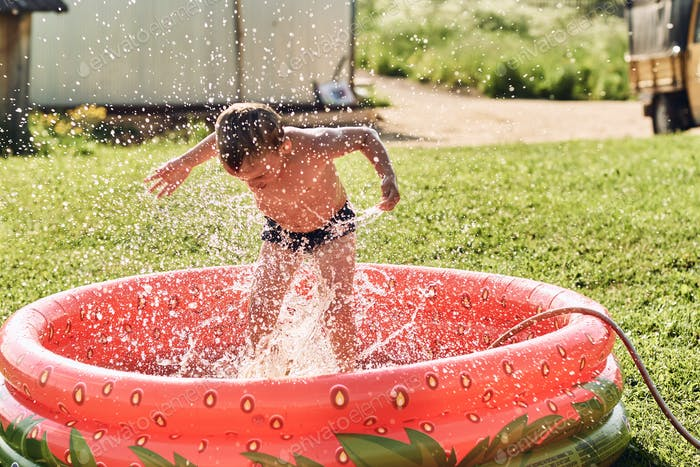A boy frolics in a small red rubber pool in the summer.