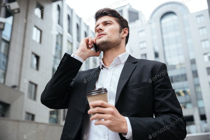 Businessman with take away coffee talking on cell phone