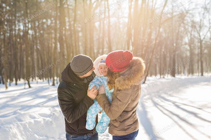 mother and father holding their baby boy and kissing his outside in the winter