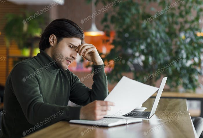 Young sad businessman having troubles with documents
