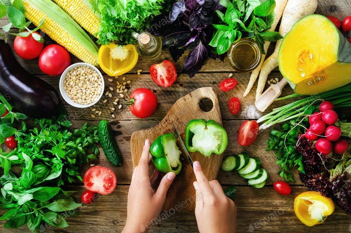 Woman hands cutting vegetables on wooden background. Vegetables cooking ingredients, top view, copy
