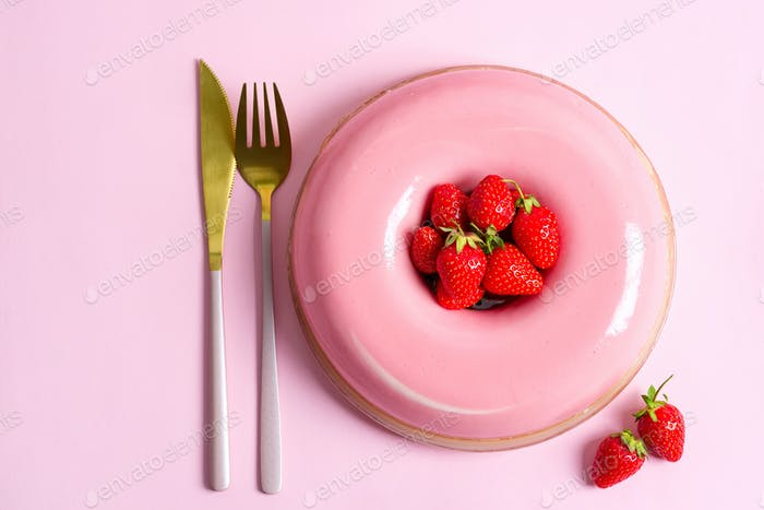 Freshly prepared homemade strawberry fruit dessert with golden fork and knife on a pink background