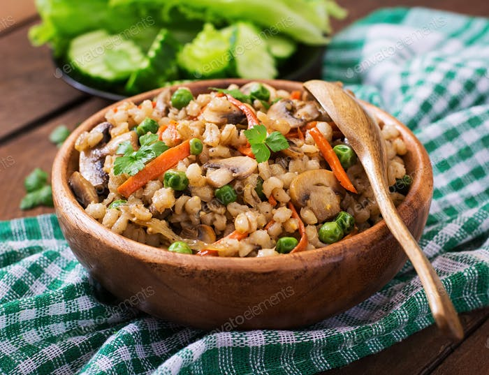 Vegetarian crumbly pearl barley porridge with mushrooms and green peas in a wooden bowl