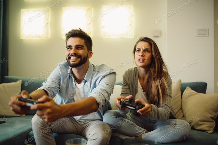 Who will win? Young couple is competing in playing video games at home