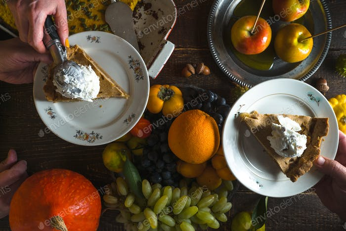 Pieces of apple pie with ice cream on plates, vegetables and fruits on Thanksgiving Day